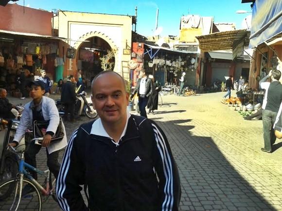 Fred no meio de uma rua, com um menino de bicicleta atrás e uma construção árabe ao fundo Blog Vem Por Aqui
