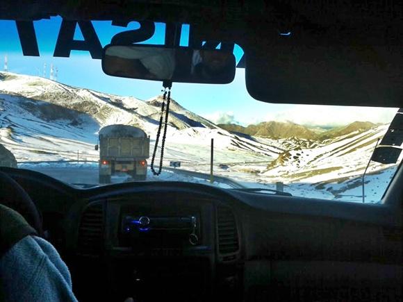 Visão do lado de dentro da van, com parabrisa na frente, caminhão e montanhas do lado de fora Blog Vem Por Aqui