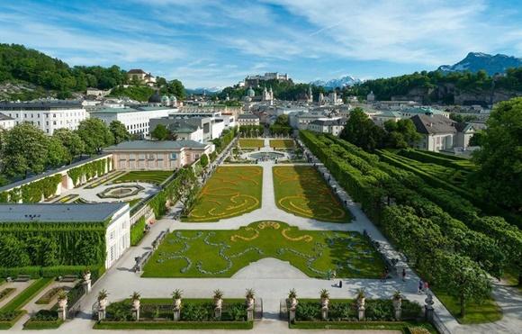 Vista do alto dos jardins de Mirabell com arbustos coloridos e podados em formas diferentes, como arabescos Blog Vem Por Aqui