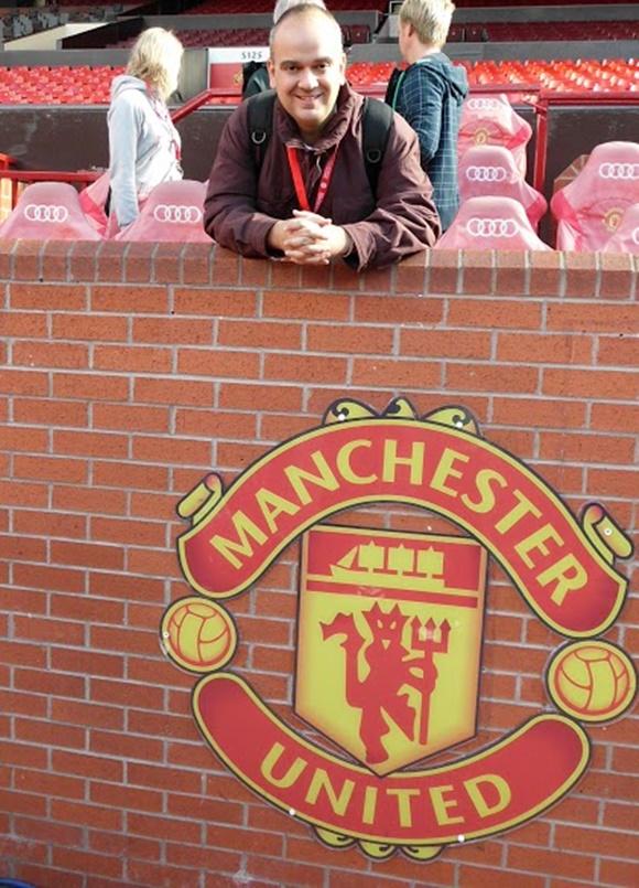 Fred, pendurado no murinho de tijolo diante do banco de reservas onde está o escudo do time Blog Vem Por Aqui