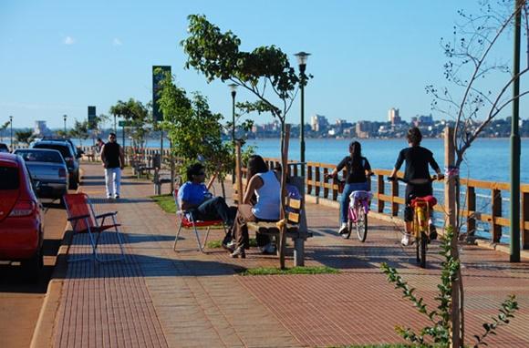 Pessoas andando de bicicleta e sentadas num banquinho no calçadão à beira mar de Posadas Blog Vem Por Aqui