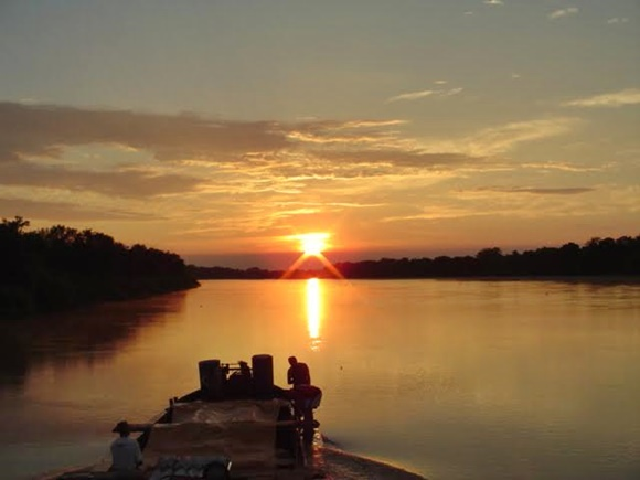 Sol se pondo no Rio Paraguai e barco passando nas águas Blog Vem Por Aqui