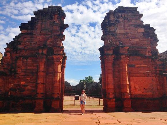Sana no meio do pórtico das ruínas de San Ignácio Blog Vem Por Aqui