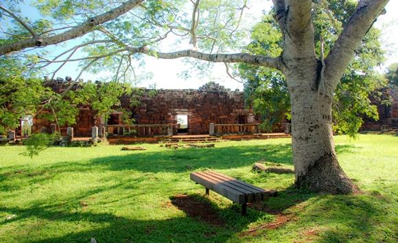 Parque com árvore grande e banco embaixo. Ao fundo uma parede de ruínas Blog Vem Por Aqui