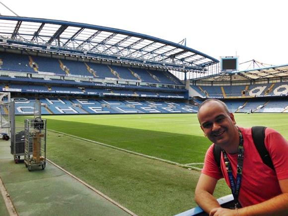 Fred, encostado na lateral do campo, com gramado e arquibancada ao fundo, na arquibancada está escrito Chelsea Blog Vem Por Aqui