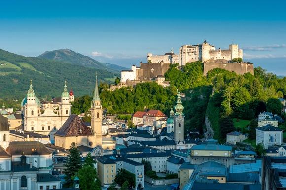 Vista do alto da cidade com castelo destacado no topo de uma colina ao fundo e prédios embaixo Blog Vem Por Aqui