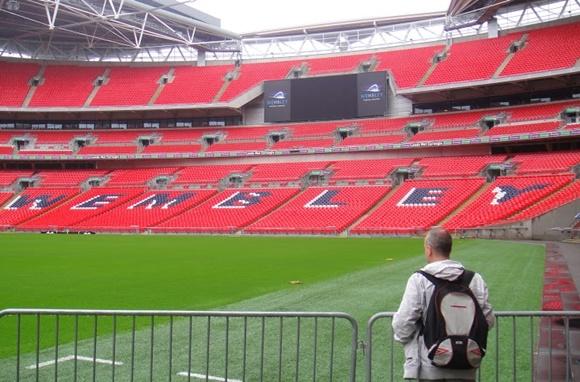 Fred de costas, diante de uma grande olhando o gramado e a arquibancada vermelha onde está escrito Wembley Blog Vem Por Aqui