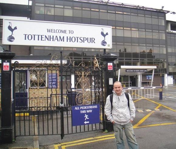 """Fred em frente a um portão que acima tem uma placa dizendo """"Welcome to Tottenham Hotspur Blog Vem Por Aqui"""