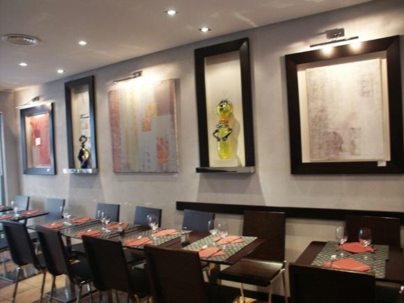 Parte interna do restaurante com mesas e cadeiras próximas à parede e obras de arte acima Blog Vem Por Aqui