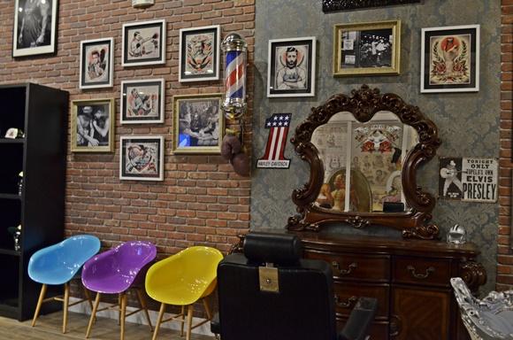 Espaço com penteadeira antiga e cadeira de barbeiro preta em frente, quadros na parede e cadeiras redondas ao lado coloridas Blog Vem Por Aqui