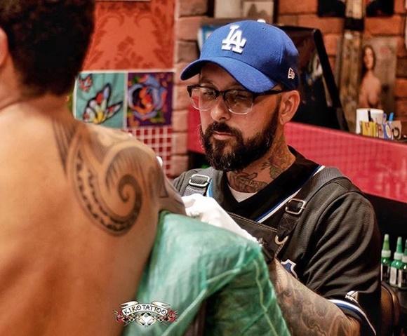 Kiko de boné e óculos de grau tatuando o braço de uma pessoa