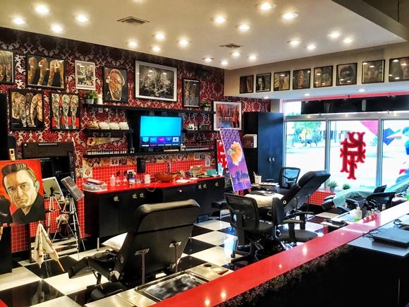 Interior da loja com cadeiras de tatuagem e parede de quadros Blog Vem Por Aqui
