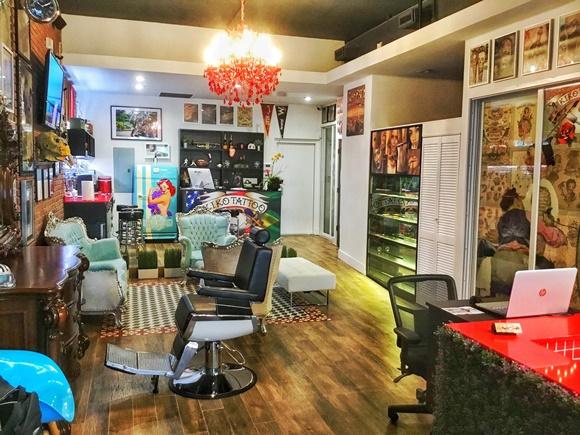 Interior da loja com cadeira de barbeiro, poltronas verdes e ao fundo uma porta de vidro em frente ao balcão com a logomarca que é a sala de esterilização Blog Vem Por Aqui