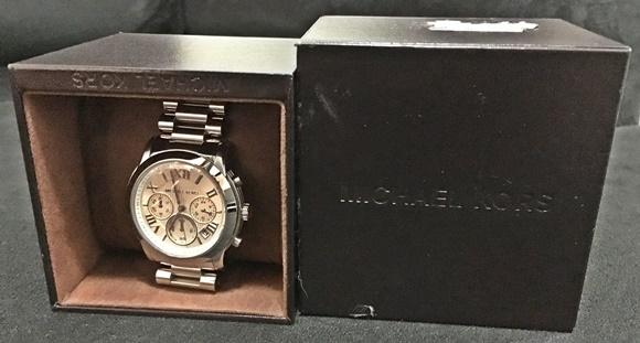 Caixa aberta, de um lado a parte central com o relógio dentro, do outro, a capa com a marca gravada apresentando amassados Blog Vem Por Aqui