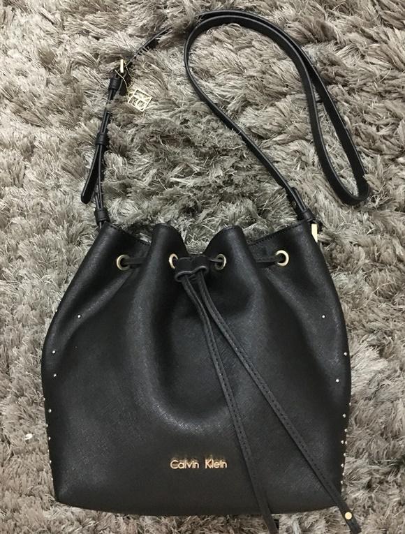 Foto de bolsa preta tipo saco com pequenas tachinhas douradas na lateral e alça comprida dobrada acima Blog Vem Por Aqui