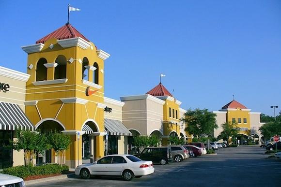 Outlet com lojas entremeadas por pequenas torres amarelas de telhados vermelhos Blog Vem Por Aqui
