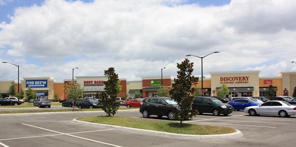 Estacionamento com pouco carros à frente e lojas ao fundo Blog Vem Por Aqui
