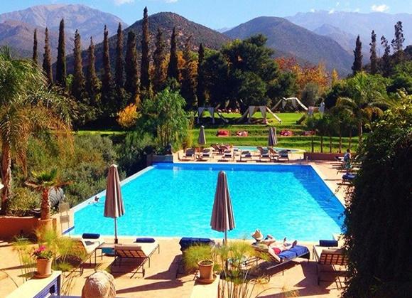 Piscina de hotel com espreguiçadeiras espalhadas e montanhas ao fundo Blog Vem Por Aqui