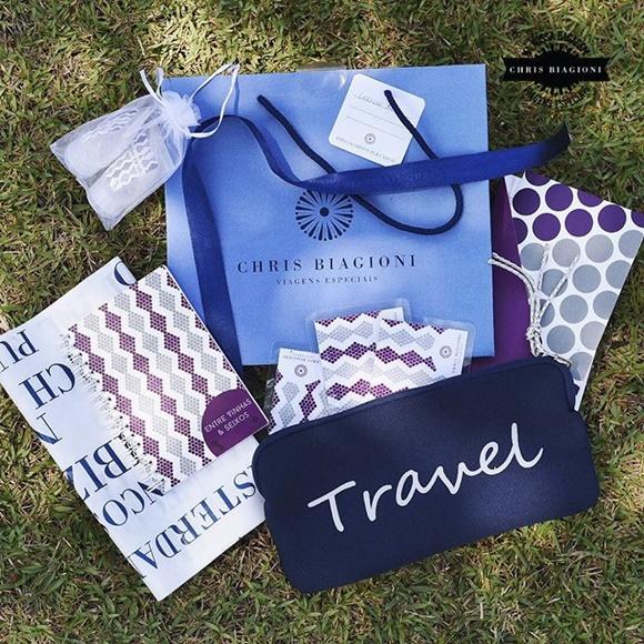 Sacolinha azul com a logo e o nome da agência cercada por caderno, papéis e uma necessaire com a palavra Travel Blog Vem Por Aqui