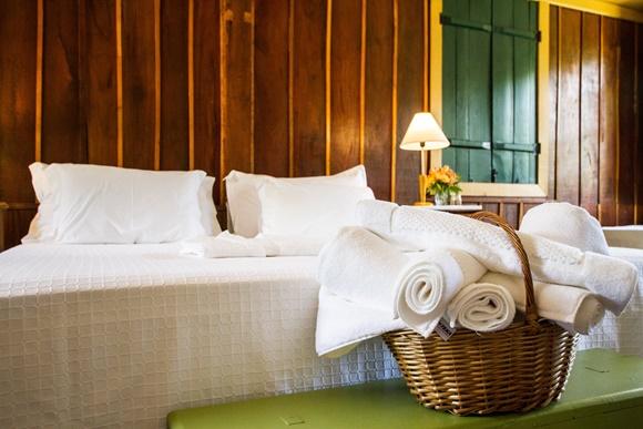 Close da cama com cesto com toalhas na frente Blog Vem Por Aqui