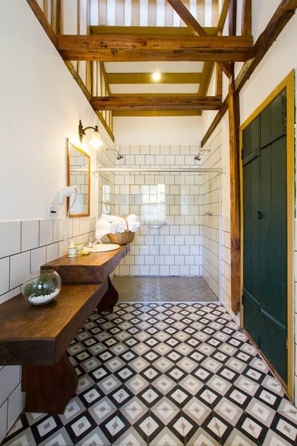 Banheiro comprido com ladrilhos preto e branco, porta verde com moldura amarela, bancada da pia em madeira de lei, chuveiro duplo Blog Vem Por Aqui