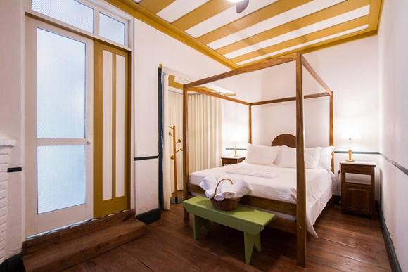 Quarto com cama com dossel de madeira e banco verde nos pés com a roupa de banho Blog Vem Por Aqui
