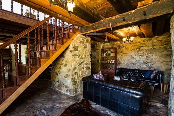 Sala embaixo da escada com coluna de pedra, sofás pretos e estante de madeira ao fundo Blog Vem Por Aqui