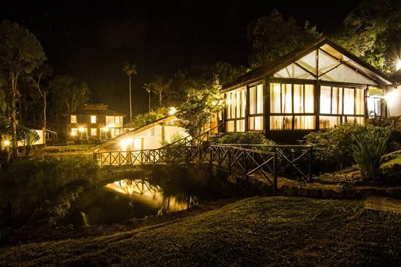 Restaurante iluminado à noite com ponte e lago em frente Blog Vem Por Aqui