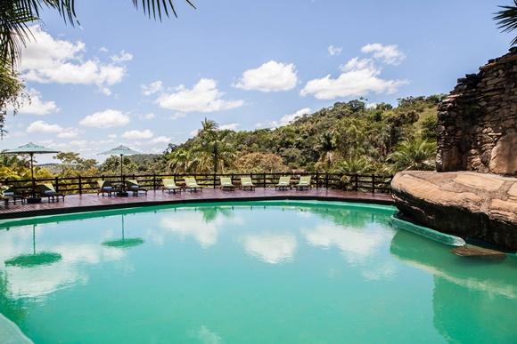 Piscina de águas natural com fundo verde e espriguiçadeiras ao fundo Blog Vem Por Aqui