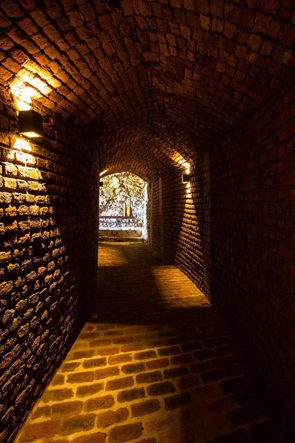 Túnel escuro, todo de tijolinhos, iluminado por pequenas luminárias na lateral Blog Vem Por Aqui