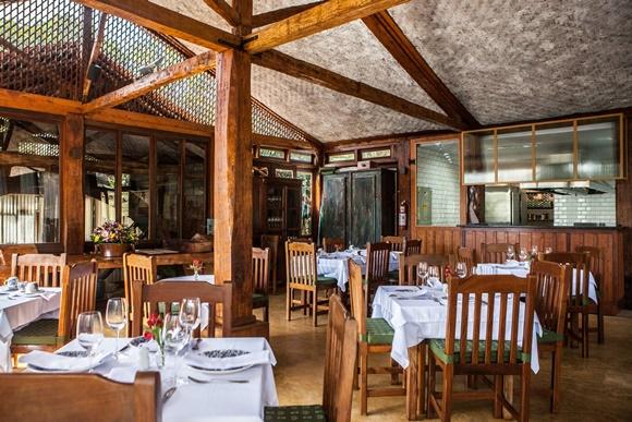 Salão do restaurante com vigas de madeira, teto baixo sem forro e mesas de madeira, montadas com toalhas brancas, copos e pratos Blog Vem Por Aqui