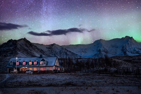 Casa no meio das montanhas com luzes acesas do lado de dentro com aurora boreal do lado de fora Blog Vem Por Aqui
