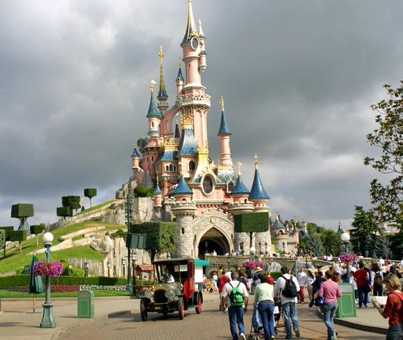 Castelo da EuroDisney com pessoas de costas caminhando em direção a ele Blog Vem Por Aqui