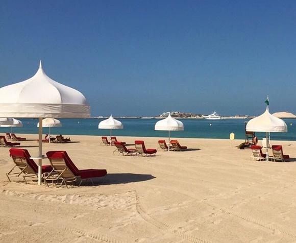 Praia privativa de um hotel em Dubai com espriguiçadeiras vermelhas e barracas pontudas brancas Blog Vem Por Aqui