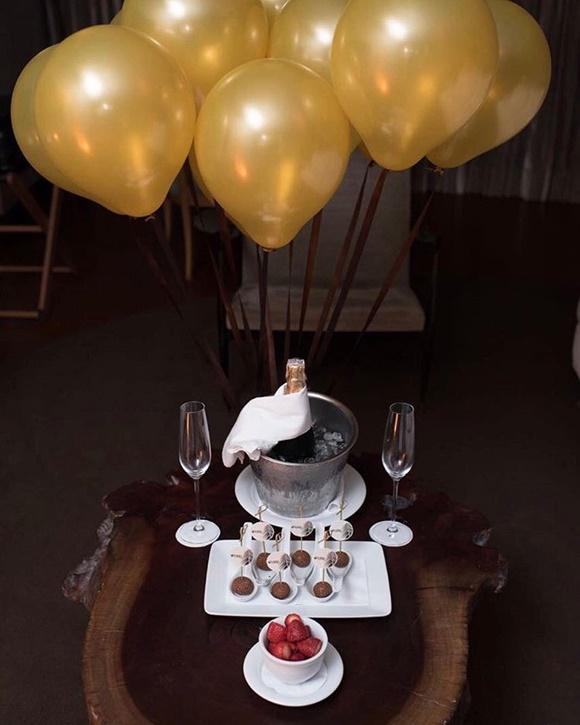 Mesa de madeira com bandeja de trudas, taças e balde de gelo com espumante e, acima, bolas de soprar douradas Blog Vem Por Aqui