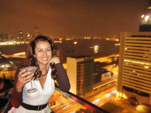 Cláudia na sacada de um apartamento com uma taça de martini, sorrindo com outros prédios desfocados ao fundo Blog Vem Por Aqui