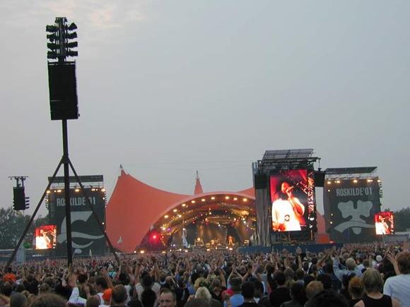 Pessoas em frente ao palco de um festival com cartaz do Bob Marley do lado Blog Vem Por Aqui