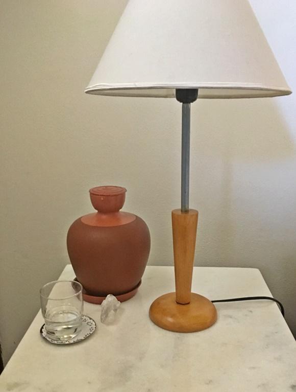 Mesa de cabeceira com tampo de mármore, abajur com pé de madeira e cúpula branca, moringa de barro, copo de vidro na frente e pedaço de cristal Blog Vem Por Aqui