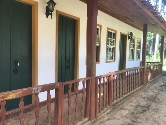 Fachada da ala das cocheiras com portas verdes e pequena grade de madeira na frente Blog Vem Por Aqui