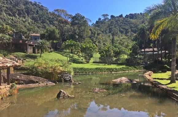 Lago rodeado por grama verde com floresta ao fundo Blog Vem Por Aqui