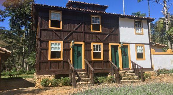 Frente da área do paiol com pequenas escadas de pedra e corrimão de madeira em frente ao prédio todo em madeira com portas verdes e janelas de moldura amarela Blog Vem Por Aqui