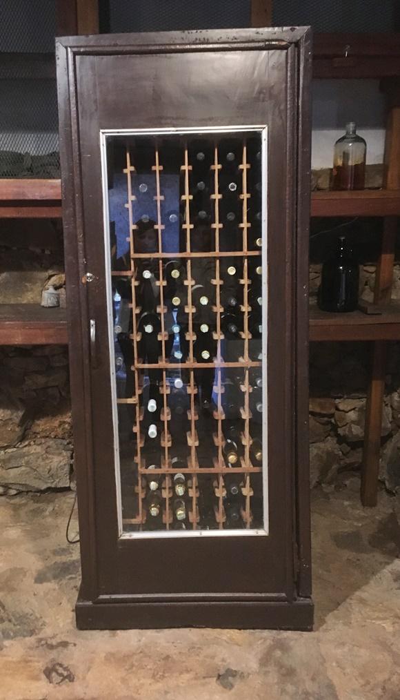 Adega tipo armário de madeira com vinhos Blog Vem Por Aqui