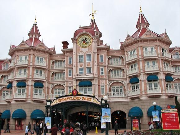 Prédio rosa e branco grande com letreiro Disneyland Park na porta Blog Vem Por Aqui