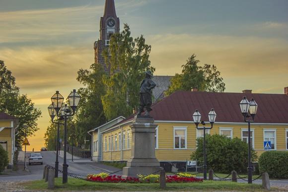 Casa amarela em frente a uma praça com uma estátua e por do sol ao fundo Blog Vem Por Aqui