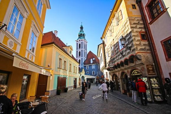 Centro e Cesky com pessoas caminhando em meio a prédios antigos e torre no fundo Blog Vem Por Aqui