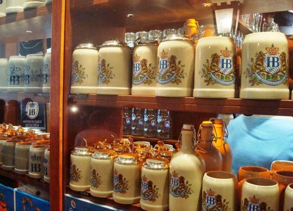 Prateleira cheia de garrafas, canecas e outras peças de cerâmica com a marca da cervejaria Blog Vem Por Aqui