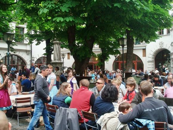 Biergarten da cervejaria com mesas lotadas debaixo de uma árvore Blog Vem Por Aqui