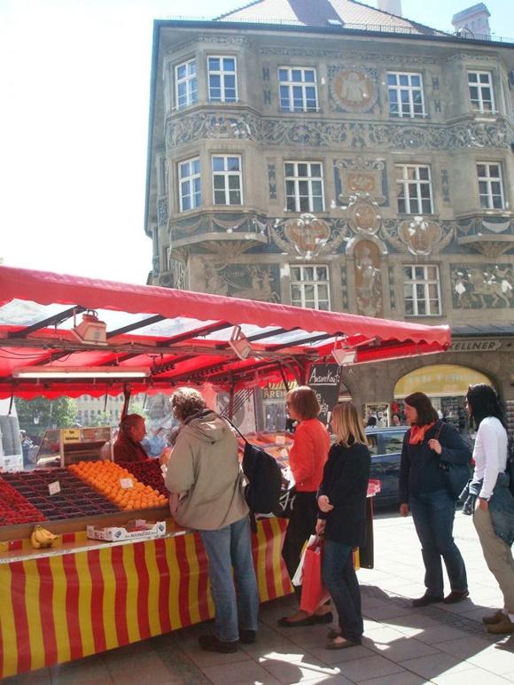 Pessoas diante de uma barraquinha de frutas Blog Vem Por Aqui