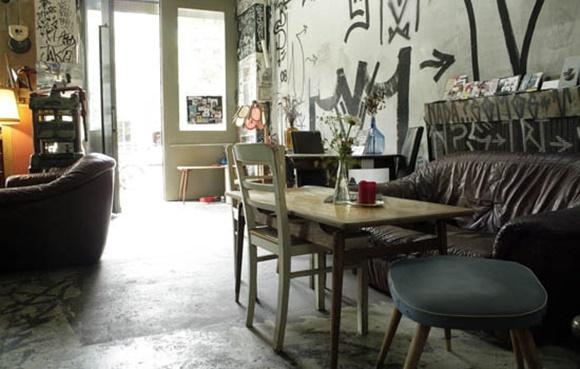 Sofá velho com mesa e cadeiras na frente dentro do bar Blog Vem Por Aqui
