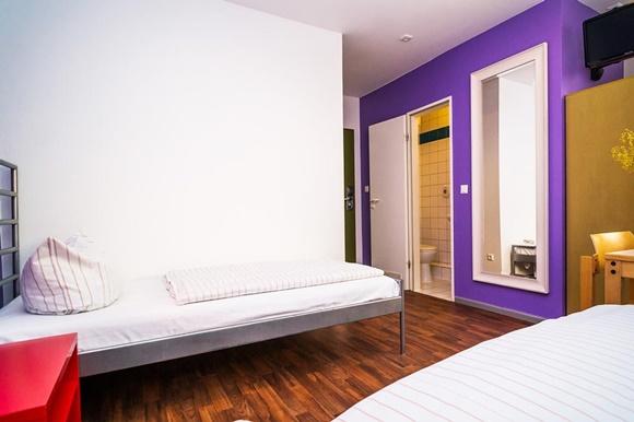 Camas do quarto com banheiro e espelho na frente Blog Vem Por Aqui